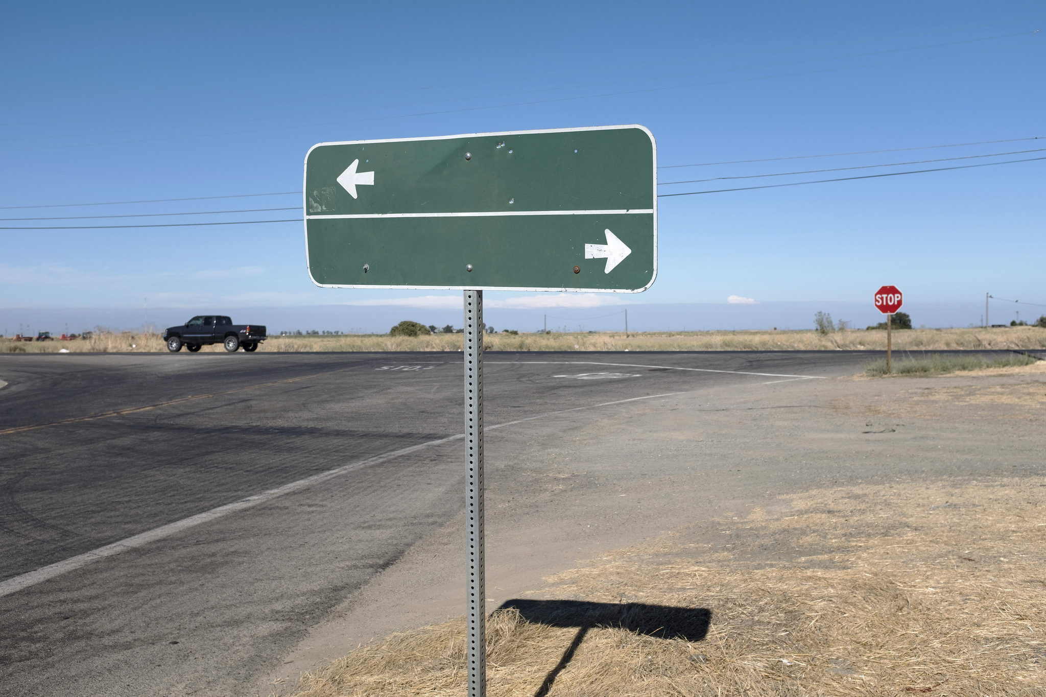 Image of road sign with no words, just two arrows pointing in opposite directions on an empty road.