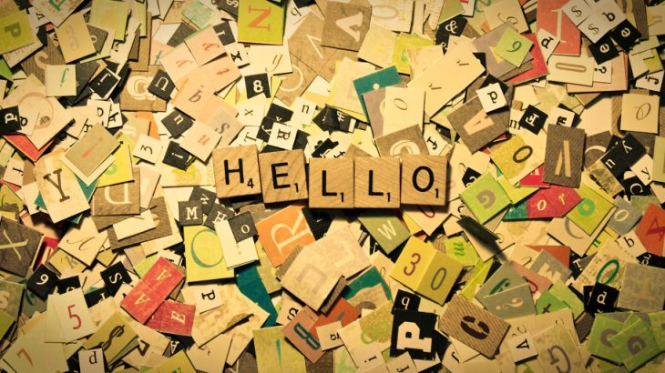 "Image of cut out letters covering a surface, on top of them are Scrabble titles with letters spelling out the word ""Hello"""