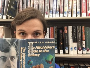 Blog post author Stephanie posing in front of science fiction bookshelf with a book in front of her face