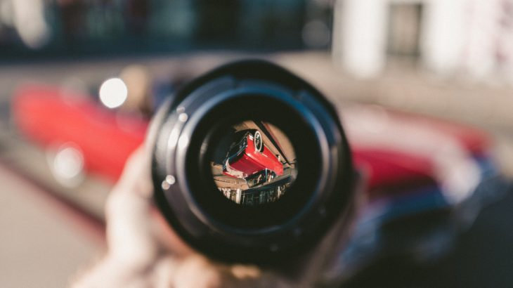 looking at a red car through a camera lens shown upside down and focused surrounded by a blurred view.